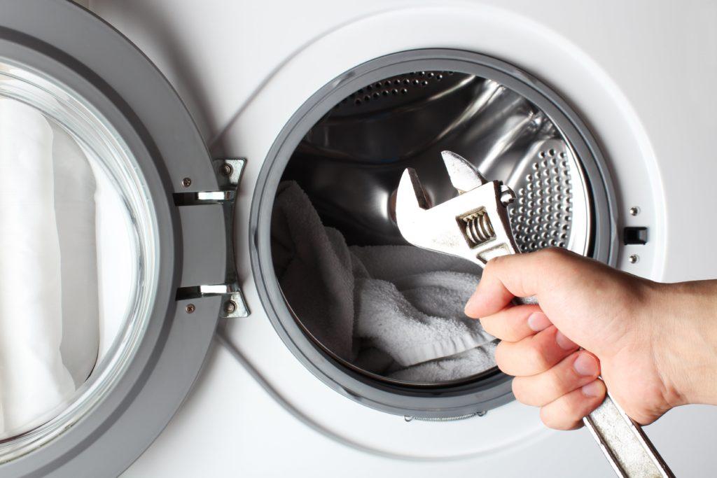 Arbeiter von Reci Haustechnik sind dabei eine Waschmaschine zu reparieren